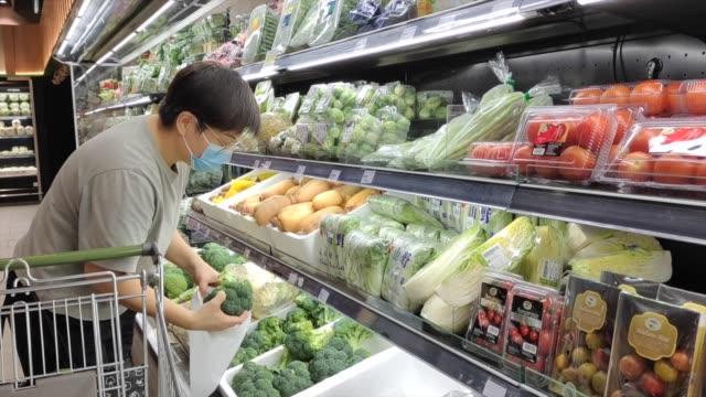 eine asiatische chinesische frau trägt eine maske gehen einkaufen im supermarkt kaufen lebensmittel - malaysia stock-videos und b-roll-filmmaterial