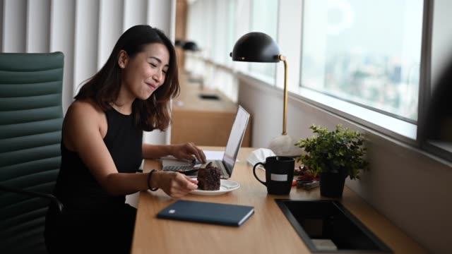 アジアの中国の女性ホワイトカラー労働者若いエグゼクティブは、社会的な離散性が適用された午後に共同共有作業室で彼女のワークステーションで働いている間、彼女のチョコレートケー� - white collar worker点の映像素材/bロール