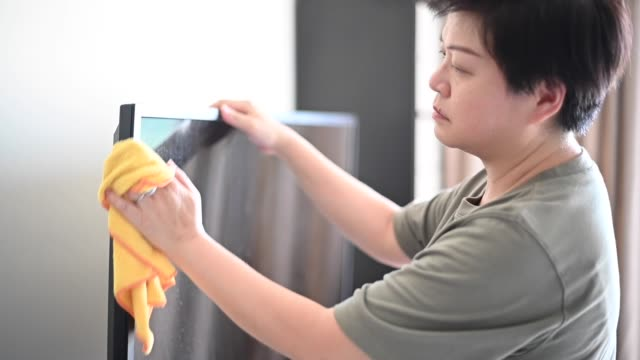 an asian chinese female wiping cleaning her television with a microfiber cloth - cleaning agent stock videos & royalty-free footage