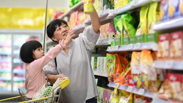 vídeos de stock, filmes e b-roll de uma avó chinesa asiática e neta compras em uma mercearia selecionando e comprando produto diário - etiqueta mensagem