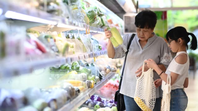 an asian chinese grandmother and granddaughter shopping in a grocery shop refrigerator vegetables department selecting and buying vegetables - reusable bag stock videos & royalty-free footage