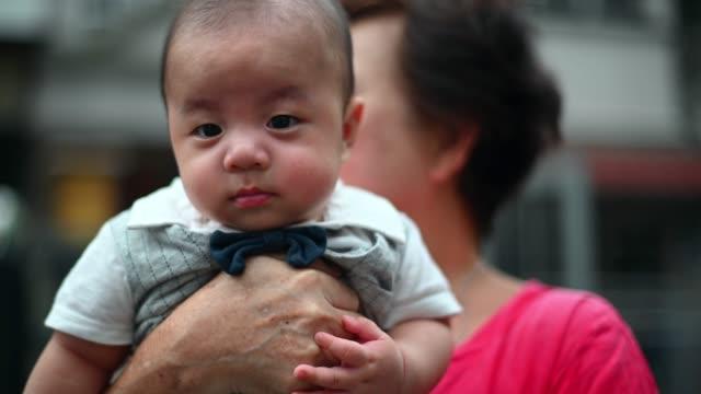 vidéos et rushes de une grand-mère chinoise asiatique portant son petit-fils bébé à la cour avant de sa maison - tenir