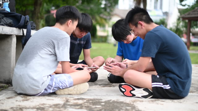 an asian chinese group of teenage boys playing mobile game in the basketball court after school using phone generation z - teenage boys stock videos & royalty-free footage