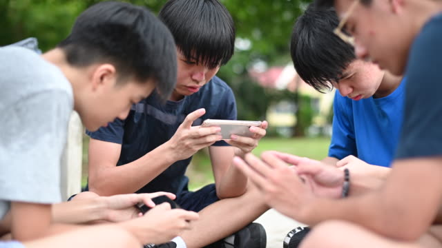 an asian chinese group of teenage boys playing mobile game in the basketball court after school using phone generation z - dependency stock videos & royalty-free footage