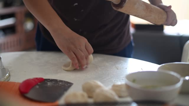 an asian chinese house wife preparing food using rolling pin with flour mixed with eggs on table making dough - rolling pin stock videos & royalty-free footage
