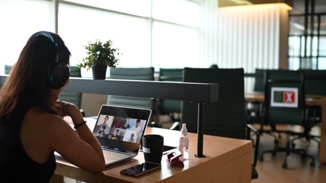vídeos y material grabado en eventos de stock de una asiática china mujer de pelo largo que tiene videoconferencia con sus socios de negocios en la oficina de coworking - evento virtual