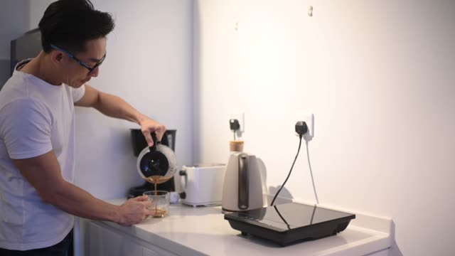 an asian chinese male pouring coffee at his kitchen - caffeine molecule stock videos & royalty-free footage