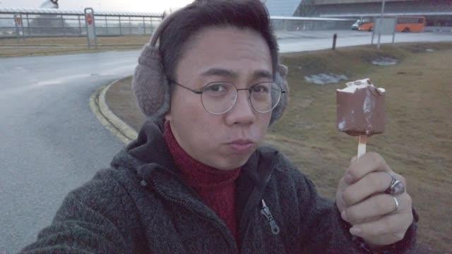 vídeos de stock, filmes e b-roll de um macho chinês asiático que anda e que aprecia o gelado no tempo frio - protetor de ouvido
