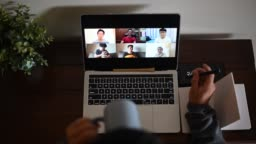 An asian chinese male working at home using laptop video conference call meeting with headset