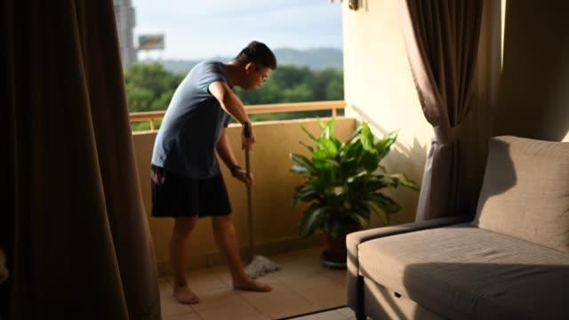 vídeos de stock, filmes e b-roll de um homem chinês asiático esfregando sua varanda durante a ordem de movimento restrito na malásia durante o pôr do sol - chão de cerâmica