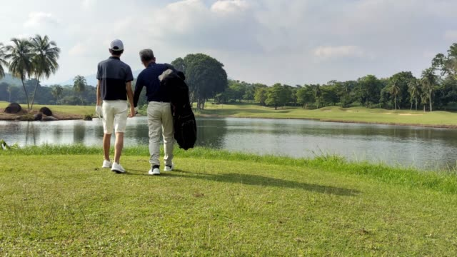 an asian chinese man with his teenager son walking toward golf course for the game carrying golf bag looking at view - golf shoe stock videos & royalty-free footage