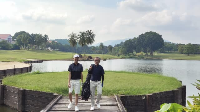 an asian chinese man with his teenager son walking toward golf course for the game carrying golf bag looking at view - golf bag stock videos & royalty-free footage