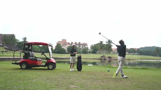 an asian chinese mature adult selecting driver golf club from golf bag for tee off and guiding teaching his son at the golf course tee off point - golf bag stock videos & royalty-free footage