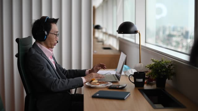 an asian chinese mid adult businessman having video conference with his colleague and business partners  in the office using headset and laptop - challenge stock videos & royalty-free footage