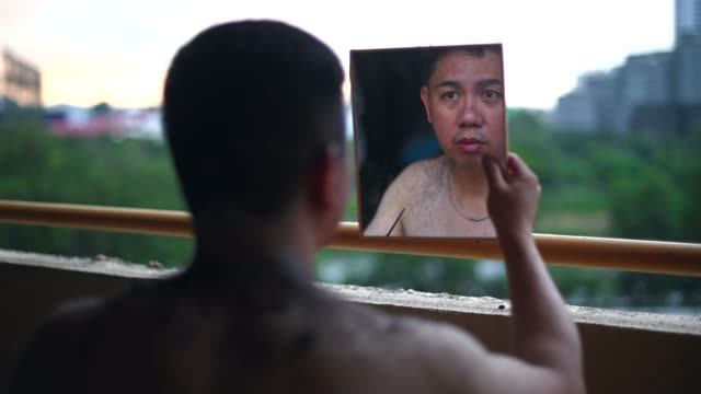 an asian chinese mid adult cutting his own hair during the quarantine at his living room balcony with a pair of scissors, mirror in the evening - self love stock videos & royalty-free footage