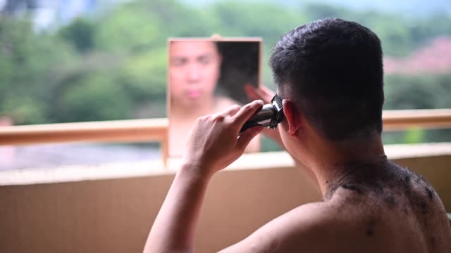 an asian chinese mid adult cutting his own hair during the quarantine at his living room balcony with a hair trimmer , mirror in the evening - self love stock videos & royalty-free footage