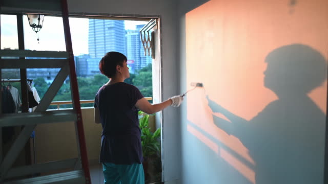 an asian chinese mid adult female painting her living room, apartment renovation during sunset - decorating stock videos & royalty-free footage