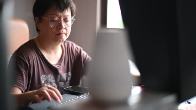 an asian chinese mid adult female working in her home office in front of desktop pc - in front of stock videos & royalty-free footage
