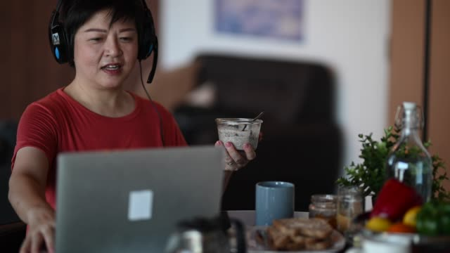 an asian chinese mid adult having breakfast in dining room while using laptop to reply emails in the morning - routine stock videos & royalty-free footage