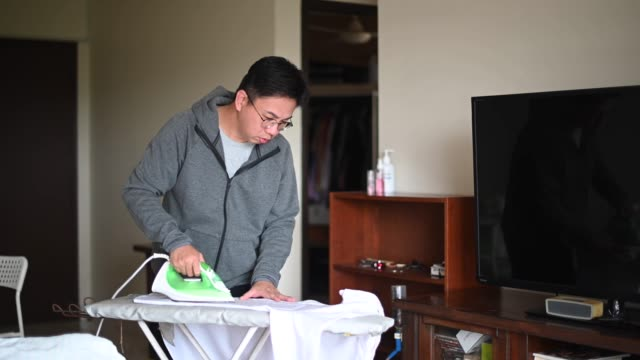 an asian chinese mid adult ironing his button down white shirt - white shirt stock videos & royalty-free footage
