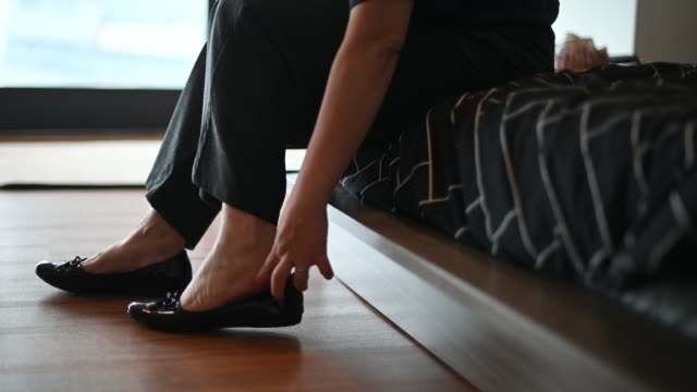 an asian chinese mid adult is getting ready wearing her shoes before leaving her apartment to work - footwear stock videos & royalty-free footage