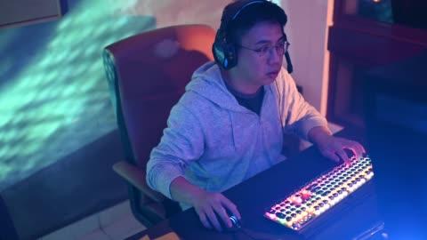 en asiatisk kinesisk mitten vuxen man hemma spelar dataspel på sitt arbetsrum med headset online prata med sina lagkamrater - persondator bildbanksvideor och videomaterial från bakom kulisserna