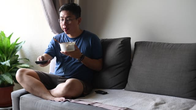 vídeos de stock e filmes b-roll de an asian chinese mid adult man having his take out food while pressing tv remote control watching tv on sofa - one mid adult man only