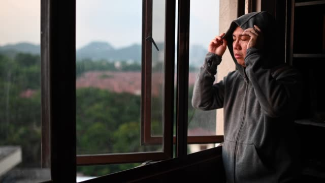 an asian chinese mid adult man looking outside of window from his home during sunset with serious facial expression with hooded shirt - hopelessness stock videos & royalty-free footage