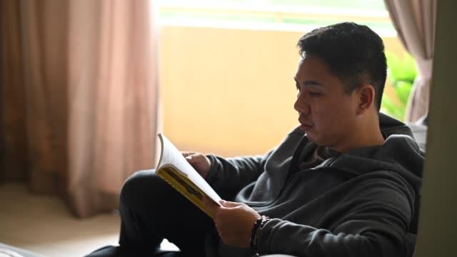 vidéos et rushes de un homme chinois asiatique moyen adulte affichant un livre dans l'après-midi sur son sofa dans le salon - littérature