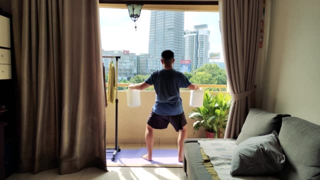 vídeos de stock e filmes b-roll de an asian chinese mid adult man using 2 detergent cleaner bottle as weight dumbbell for body weight training at balcony - sports training