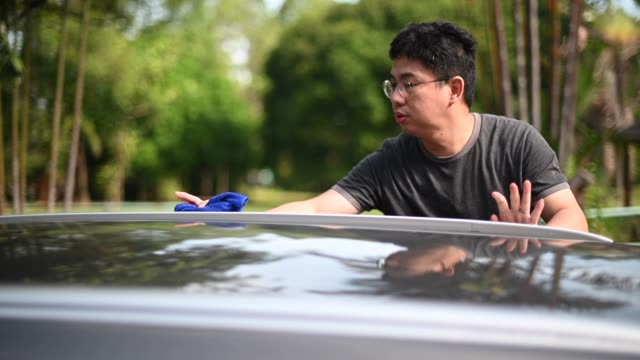 an asian chinese mid adult man washing and cleaning car in front of his house - environmental conservation stock videos & royalty-free footage