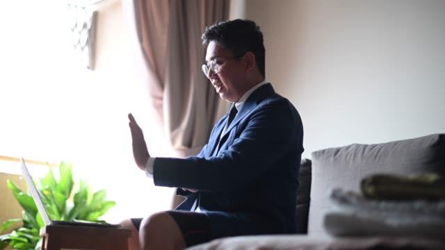 vidéos et rushes de un homme chinois asiatique moyen adulte avec la cravate et le costume et le pantalon court s'asseyant sur le sofa utilisant l'ordinateur portatif dans son salon pour la vidéoconférence avec son associé et collègue réunion virtuelle d'affaires - short
