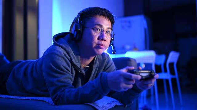 vídeos de stock, filmes e b-roll de um adulto asiático chinês médio jogando videogame em casa sozinho à noite na escuridão com fone de ouvido e controlador de jogo sentado no sofá deitado - concentração