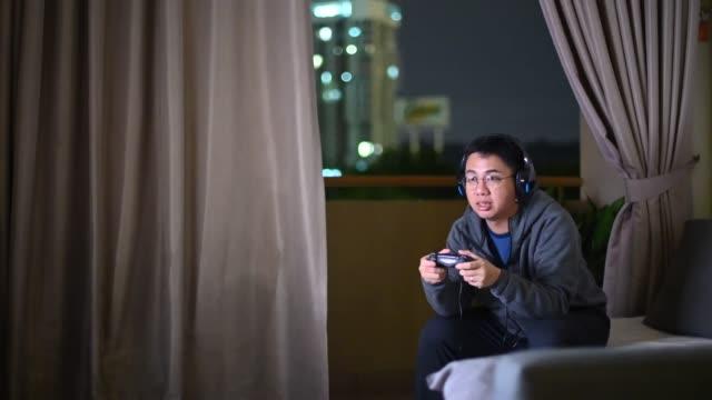vídeos de stock, filmes e b-roll de um adulto asiático chinês médio jogando videogame em casa sozinho à noite na escuridão com fone de ouvido e controlador de jogo sentado no sofá - concentração