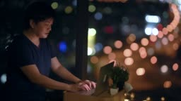 an asian chinese mid adult surfing the net using laptop at night in the apartment near the window with cityscape view
