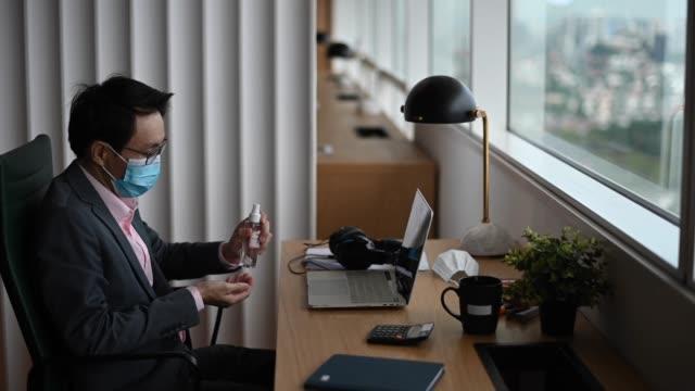 アジアの中国の中年の白人の白い襟の男は、彼のワークステーションの前で手指消毒剤で手を掃除 - white collar worker点の映像素材/bロール