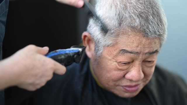 an asian chinese mid adult woman is cutting and trimming hair for her father in the kitchen due to travel ban - cutting hair stock videos & royalty-free footage