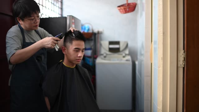 an asian chinese mid adult woman is cutting and trimming hair for her son in the kitchen due to travel ban - cutting hair stock videos & royalty-free footage