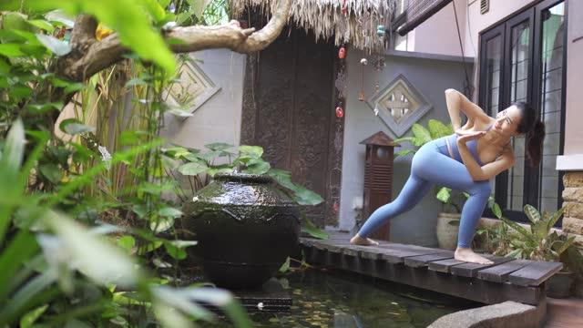 una donna asiatica cinese di mezza età che pratica yoga nel suo cortile di fronte su un ponte di legno sopra lo stagno - stagno acqua stagnante video stock e b–roll