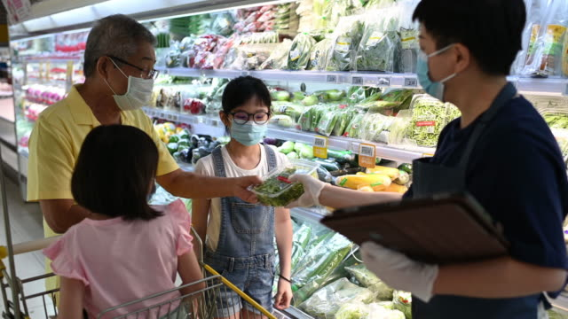 an asian chinese mid adult woman retail assistant advising and helping a family to select the vegetable from the refrigerated section in supermarket - greengrocer stock videos & royalty-free footage