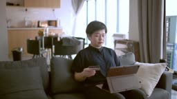 an asian chinese mid adult woman using her digital tablet and credit card to purchase online shopping payment in living room sofa