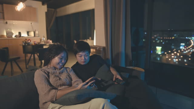 an asian chinese mid adult woman watching tv programme with her teenager daughter - teenage girl watching tv stock videos & royalty-free footage