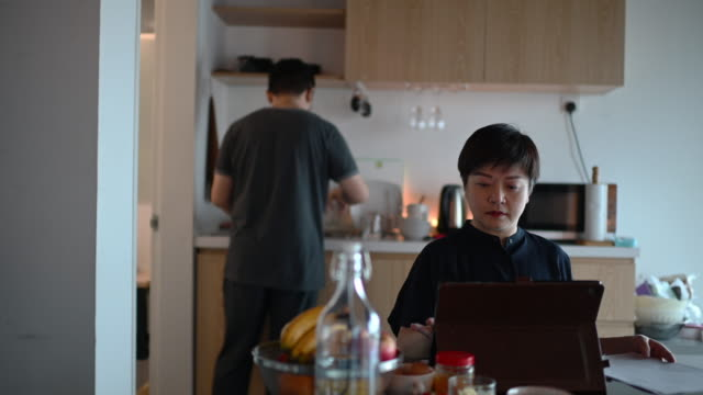 an asian chinese mid adult woman working from home at dining table using digital tablet and documents during breakfast time while her husband cleaning dishes - comfortable stock videos & royalty-free footage
