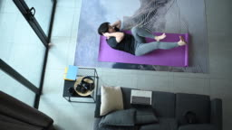 an asian chinese mid adult woman workout exercising from home and learning online exercise class