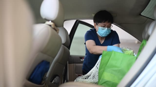 an asian chinese mid age woman removing reusable bags from her car which she just bought all groceries from supermarket with her face mask and surgical glove - reusable bag stock videos & royalty-free footage