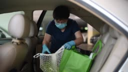 An asian chinese mid age woman removing reusable bags from her car which she just bought all groceries from supermarket with her face mask and surgical glove