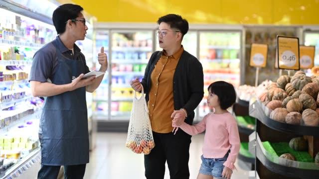 彼女の娘とアジアの中国人の母親は、アドバイスとアシスタントのためにエプロンと男性の店主と話しています - リサイクル素材点の映像素材/bロール
