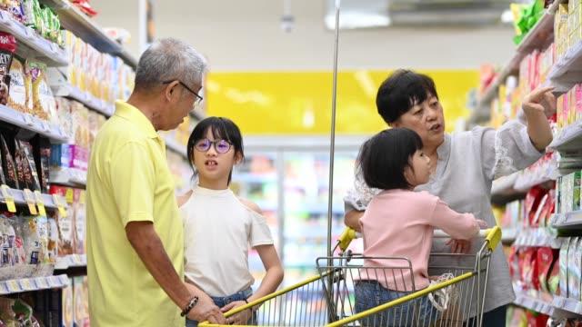 食料品屋で購入するアジアの中国の多世代家族の祖父母と孫は、アイテムや毎日の製品を選択して購入 - リサイクル素材点の映像素材/bロール