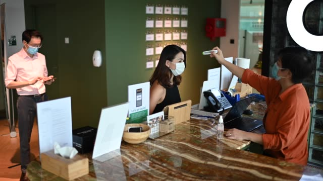 an asian chinese receptionist conducting standard operating procedure for illness prevention by measuring visitors colleague coworkers body temperature and record their personal data - hotel stock videos & royalty-free footage