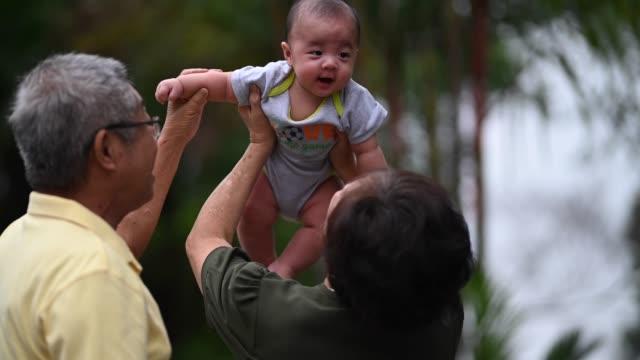 vidéos et rushes de un couple chinois asiatique aîné jouant avec leur petit-fils à la cour avant de leur maison - tenir